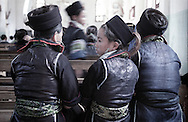 Rear view of Hmong girls wearing traditional outfit during a mass in Sapa's church. Vietnam, Asia