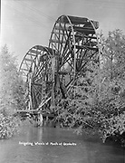 """9305-B7064. Irrigating wheels a the mouth of Deschutes River, Oregon. This was published in Belshe, Bertha """"They Paved The Way"""" pg. 29 captioned """"The Irrigation Waterwheel on the Deschutes was used for power to push the water to irrigate orchards, gardens and hay ground. Jack Alsup tells me he remembers his father using the wheel. This stood near the mouth of the Deschutes on the Sherman County side."""""""
