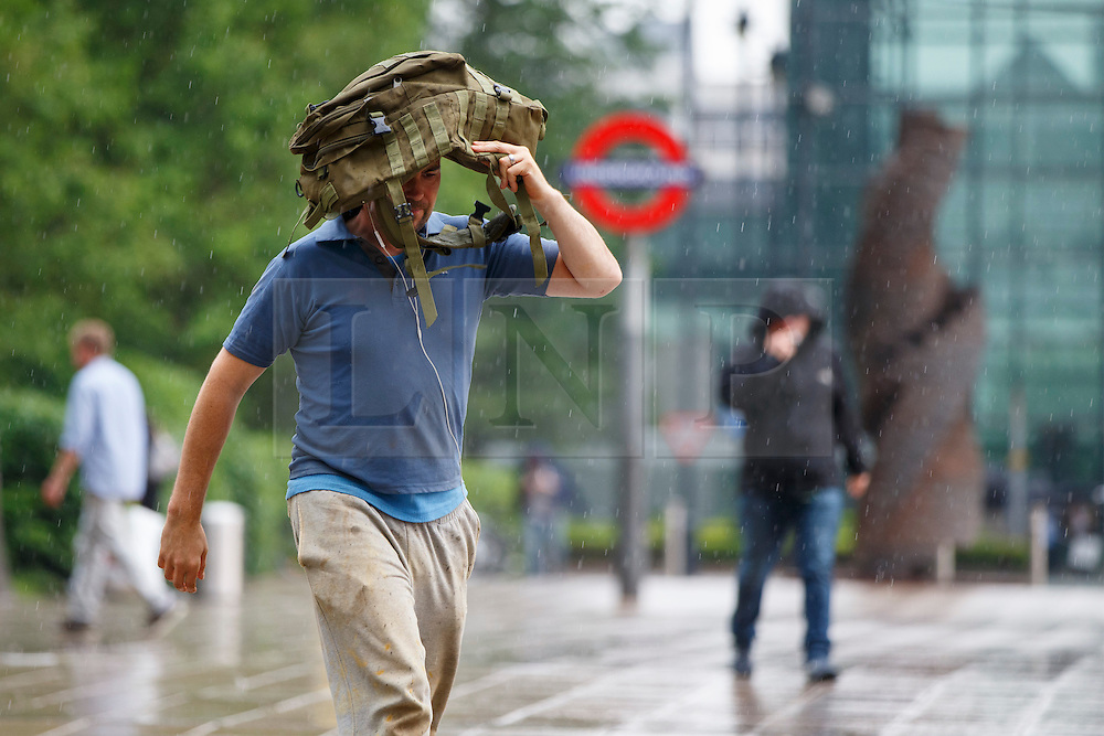 © Licensed to London News Pictures. 07/06/2016. London, UK. People taking shelter in the rain in Canary Wharf, east London on Tuesday, 7 June 2016. Photo credit: Tolga Akmen/LNP