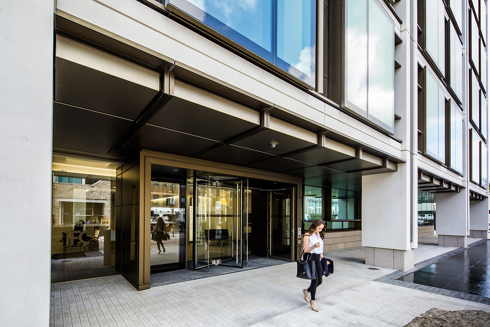Woman walking out of the International Finance Centre building in the business and banking district of St Helier, Jersey