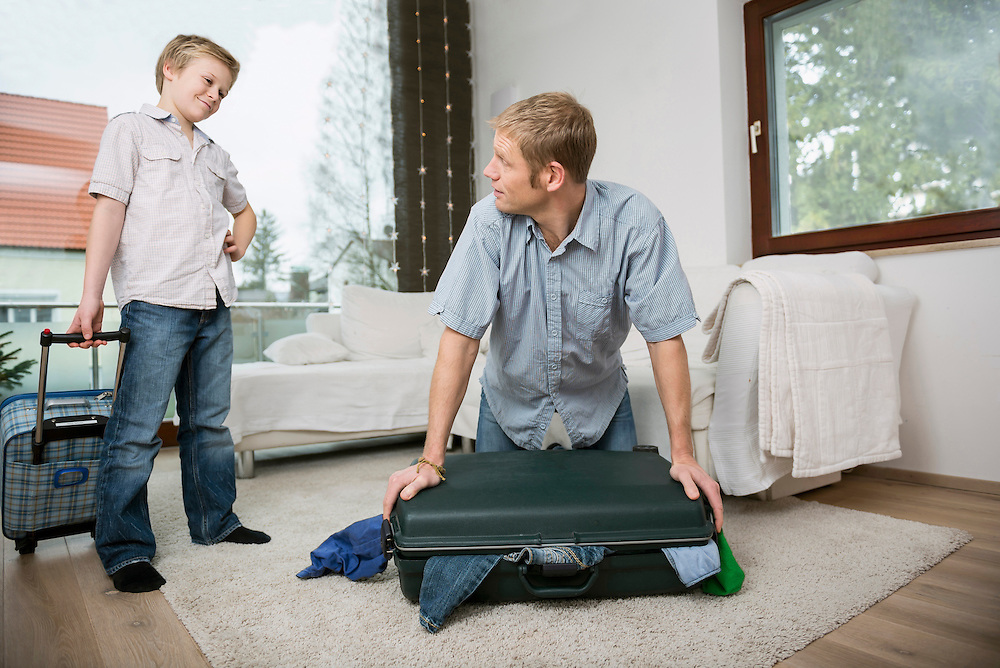 Father and son packing suitcase