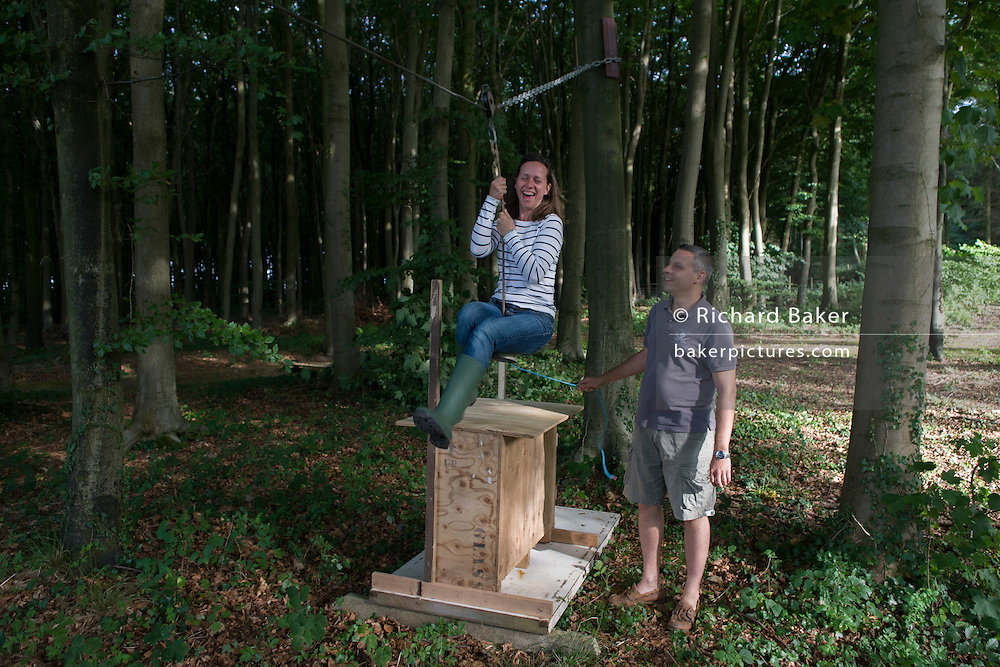 A husband and wife play in woodland on a home-made zip wire ride on private land in Somerset.