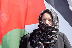 © Licensed to London News Pictures; 12/06/2021; Hayle, Cornwall UK. G7 summit in Cornwall. A woman stands in front of the Palestinian flag at the Resist G7 coalition of protest groups protest in Hayle on the second day of the G7 summit. The protest included supporters of Palestine and of Kashmir as well as anti-war groups and socialists and trade unionists. Photo credit: Simon Chapman/LNP.