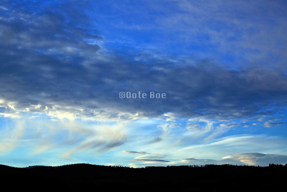 wind swept clouds against blue sky