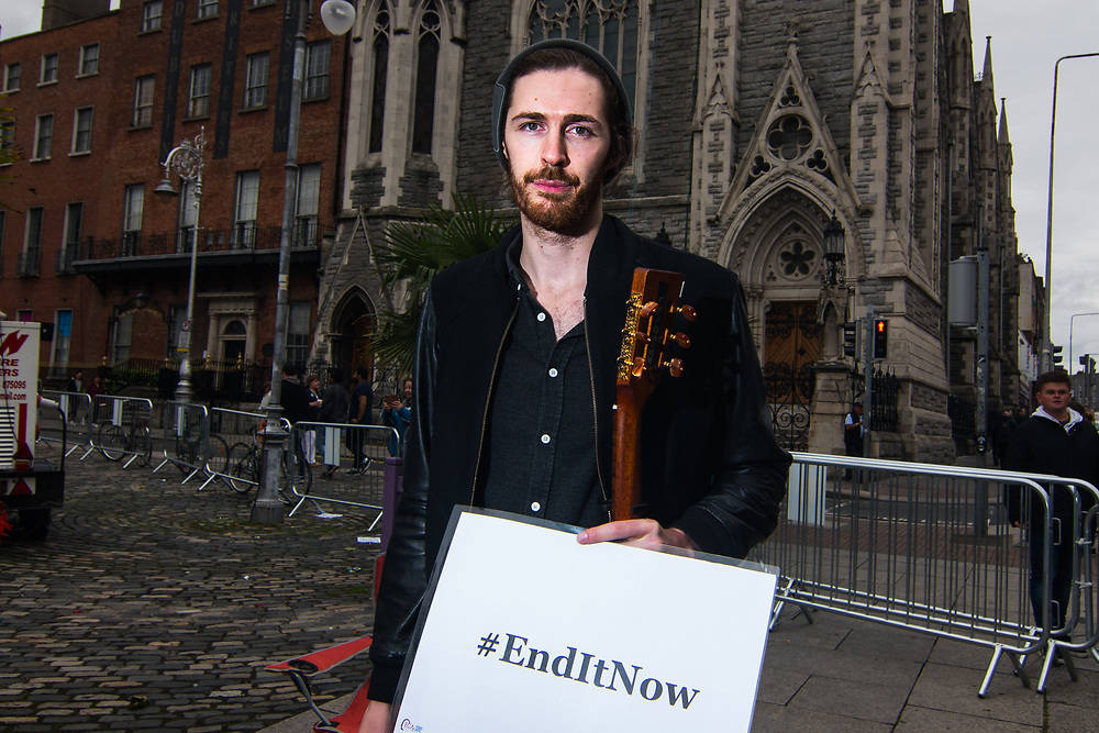 """Dublin, Ireland. 26th August, 2018. <br /> Hozier, an Irish musician, singer and songwriter, poses with a banner that say 'End It Now', slogan of the ECA global project, that aim to stop the cover-ups by Clergy, just ahead the silent protest during the Holy Mass, at the Stand4Truth protest in Garden of Remembrance, Parnell square, during the second of the two-days of the visit of Pope Francis in Dublin, Ireland.<br /> Pope Francis has made a two-day visit to the Republic of Ireland by celebrating a Mass at Dublin's Phoenix Park. The Argentine Pope asked forgiveness for the """"abuses in Ireland, abuses of power, conscience and sexual abuses"""" perpetrated by Church leaders. It was the first papal visit to Ireland for 39 years. During his activities many activists, victims and survivors have made protests and a silent march Garden of Remembrance towards the last Magdalene Laundry to close in Ireland.<br />  © Simone Padovani"""