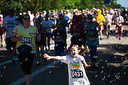 Savannah Thaler, 6, rushes through bubbles running in the 2012 Bolder Boulder 10K road race in Boulder, Colorado.