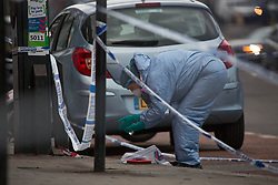 © Licensed to London News Pictures. 11/05/2021. London, UK. A forensic officer gathers evidence at a crime scene in Dollis Hill in North West London after reports of a shooting. Local media are reporting that person was rushed to hospital after an Ambulance was called at 1:52pm. A police cordon is in place on Dudden Hill Lane and on Cooper Road. Photo credit: Marcin Nowak/LNP