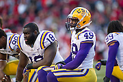 Nov 23, 2012; Fayetteville, AR, USA; Louisiana State Tigers defensive tackles Anthony Johnson (90) Bennie Logan (18) and defensive end Barkevious Mingo (49) take a knee for an injured player during a game against the Arkansas Razorbacks at Donald W. Reynolds Stadium.  LSU defeated Arkansas 20-13. Mandatory Credit: Beth Hall-US PRESSWIRE