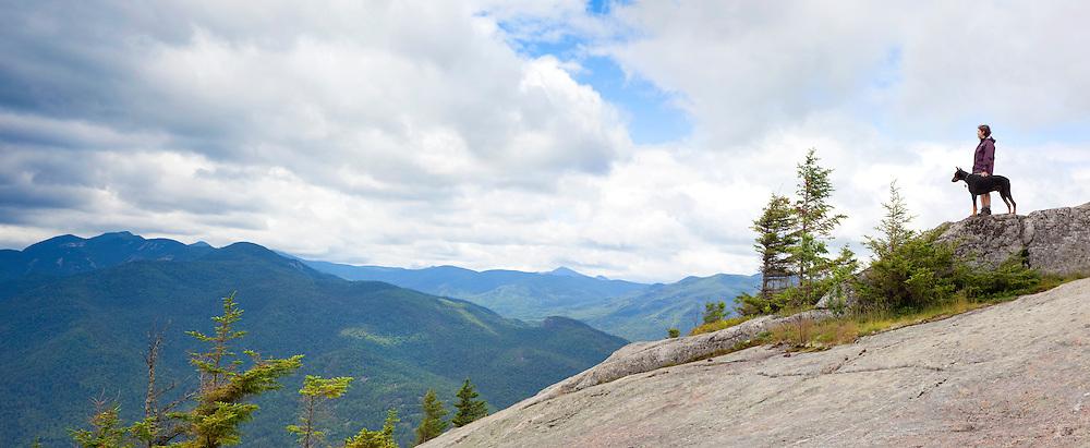 dog& hiker on mountain top