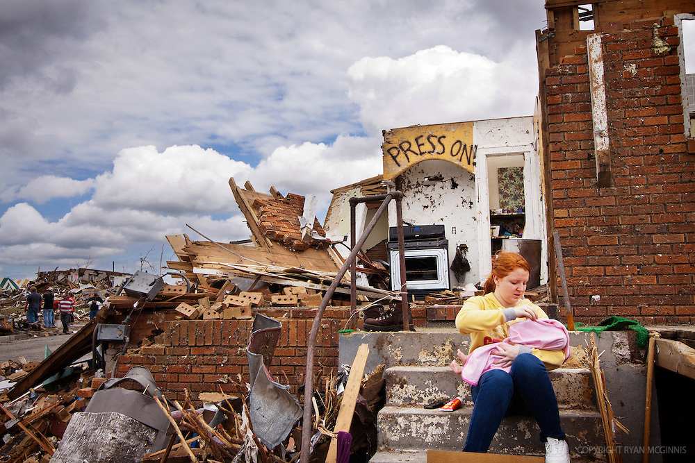 A woman holds a baby while sitting on the stoop of her destroyed home in Joplin, Missouri, May 25, 2011.  On May 22, 2011, Joplin Missouri was devastated by an EF-5 tornado.