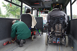 Driver securing wheel chairs in mini bus before the start of the journey,