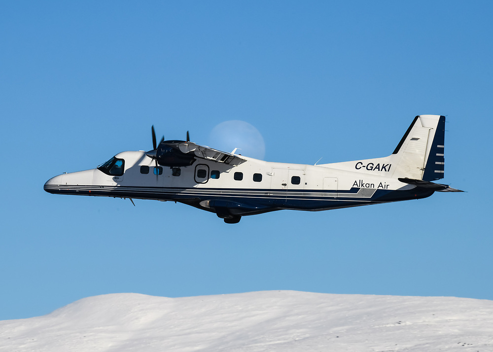 Alkan Air Ltd.'s Dornier 228 climbs past a rising moon at Erik Nielsen Whitehorse International Airport.
