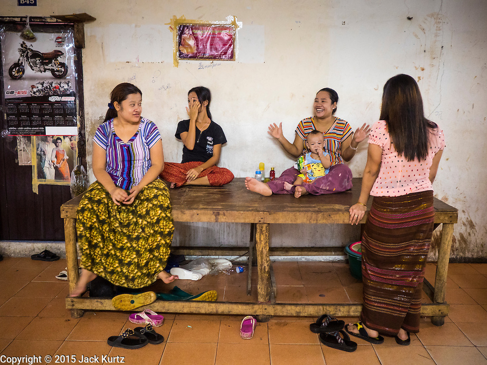 "11 JUNE 2015 - MAHACHAI, SAMUT SAKHON, THAILAND: Women who live in a tenement building used for Burmese migrant housing relax in the common space in the building. Labor activists say there are about 200,000 migrant workers from Myanmar (Burma) employed in the fishing and seafood industry in Mahachai, a fishing port about an hour southwest of Bangkok. Since 2014, Thailand has been a Tier 3 country on the US Department of State Trafficking in Persons Report (TIPS). Tier 3 is the worst ranking, being a Tier 3 country on the list can lead to sanctions. Tier 3 countries are ""Countries whose governments do not fully comply with the minimum standards and are not making significant efforts to do so."" After being placed on the Tier 3 list, the Thai government cracked down on human trafficking and has taken steps to improve its ranking on the list. The 2015 TIPS report should be released in about two weeks. Thailand is hoping that its efforts will get it removed from Tier 3 status and promoted to Tier 2 status.        PHOTO BY JACK KURTZ"
