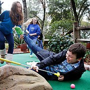 Annika Dogger, 12, of Hilton Head Island, pulls at the leg of Cooper Ealy, 9, of Princeton, N.J., after Ealy attempted to move his golf ball towards the hole by blowing on it at the Pirate's Island Adventure Golf on March 18, 2014.  Ealy is visiting old friends with his sister Caroline Ealy, 12, center, while on  spring break vacation, they moved from Hilton Head Island to Jersey years ago.