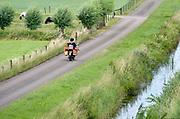 Nederland, Bemmel, 21-6-2018 Een postbode maakt op een brommer zijn ronde door het buitengebied  . FOTO: FLIP FRANSSEN