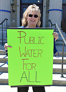 Mineola, New York, USA. April 26, 2021. CLAUDIA BORECKY, C0-Director of CAWS (Clean Air Water Soil), holds sign saying: Public Water for All at rally. Faced with a 26% rate increase from New York American Water going into effect May 1, 2021, activists and residents who are NYAW customers rally to urge NYS Assemby to push through legislation, before that date, corresponding with NYS Senate Bill S989A to establish a Nassau County Water Authority and except water works corporations in counties of populations over one million from a special franchise tax.