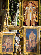 01 DECEMBER 2016 - BANGKOK, THAILAND:  A tourist walks past portraits of Bhumibol Adulyadej, the Late King of Thailand, and his son, HRH Crown Prince Maha Vajiralongkorn, who will soon be the new King of Thailand. Thailand's parliamentary body, the National Legislative Assembly, invited HRH Crown Prince Maha Vajiralongkorn to be king following the death of the Crown Prince's father, Bhumibol Adulyadej, the Late King of Thailand. The invitation marked the formal beginning of the process of naming the new King, although Crown Prince Vajiralongkorn was the heir apparent and Bhumibol's appointed successor. Shops that sell royal paraphernalia are now selling new portraits of  Crown Prince Vajiralongkorn which will be displayed alongside portraits of his late father. King Bhumipol died on Oct 13.     PHOTO BY JACK KURTZ