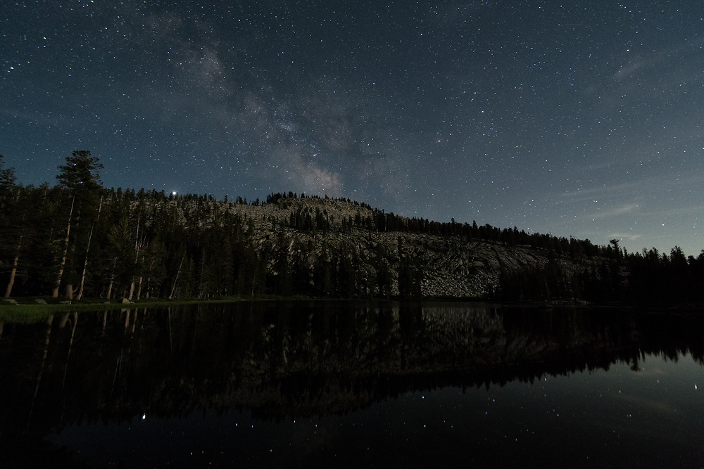 Weaver Lake in California's Jennie Lakes Wilderness beneath the Milky Way with stars reflecting on the waters.