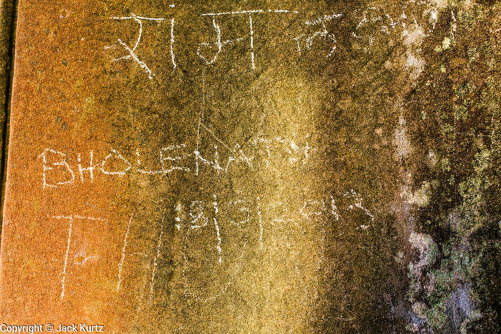 """01 JULY 2013 - ANGKOR WAT, SIEM REAP, SIEM REAP, CAMBODIA:  A tourist's graffiti on a wall in Angkor Wat. Angkor Wat is the largest temple complex in the world. The temple was built by the Khmer King Suryavarman II in the early 12th century in Yasodharapura (present-day Angkor), the capital of the Khmer Empire, as his state temple and eventual mausoleum. Angkor Wat was dedicated to Vishnu. It is the best-preserved temple at the site, and has remained a religious centre since its foundation– first Hindu, then Buddhist. The temple is at the top of the high classical style of Khmer architecture. It is a symbol of Cambodia, appearing on the national flag, and it is the country's prime attraction for visitors. The temple is admired for the architecture, the extensive bas-reliefs, and for the numerous devatas adorning its walls. The modern name, Angkor Wat, means """"Temple City"""" or """"City of Temples"""" in Khmer; Angkor, meaning """"city"""" or """"capital city"""", is a vernacular form of the word nokor, which comes from the Sanskrit word nagara. Wat is the Khmer word for """"temple grounds"""", derived from the Pali word """"vatta."""" Prior to this time the temple was known as Preah Pisnulok, after the posthumous title of its founder. It is also the name of complex of temples, which includes Bayon and Preah Khan, in the vicinity. It is by far the most visited tourist attraction in Cambodia. More than half of all tourists to Cambodia visit Angkor.      PHOTO BY JACK KURTZ"""