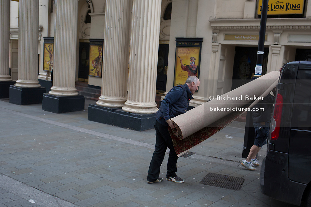 Carpet fitters carry off a rolled-up new carpet again after trimming it for the interior of the Lyceum Theatre on Wellington Street, on 5th March 2019, in London, England.