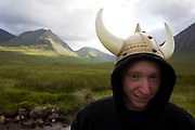 Wearing a plastic Viking horn helmet, a young man has stopped to rest amid the spectacular wilderness of Glencoe, a valley surrounded by high peaks 3,000 feet (1,000m) high mountains. The landscape is magnificent but unforgiving and walkers mainly stay on well-marked paths or, as this lad is doing - walking along the A82 road that snakes through this Scottish Glen. He admits to having trekked from Glasgow on pagan fertility Wassail rite, once performed in medieval times. This region of Britain, lake many others, was populated by Viking raiders who later settled locally and raised families whose descendents now inhabit the UK. English is full of old Norse words as are place names.