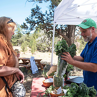 Stephanie Grenadier, left, of Candy Kitchen purchases kale and various veggies from Buffy Aakaash of WhooVille Farm at the Candy Kitchen Farmers Market, Wednesday, July 10 in Candy Kitchen. The farmers market is every Wednesday from 10 a.m. to 1 p.m.
