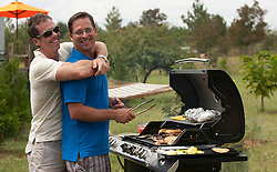 Gay couple embracing and grilling food