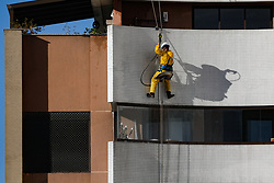May 27, 2019 - Curitiba, Brazil - CURITIBA, PR - 27.05.2019: TRABALHO EM ALTURA - Worker rinses the façade water in a garage, with the PPE&#39equired fed for work in height, according to work safety rules, he neighborhood of Agua Verde in Curitiba, Pa, PR. (Credit Image: © Rodolfo Buhrer/Fotoarena via ZUMA Press)