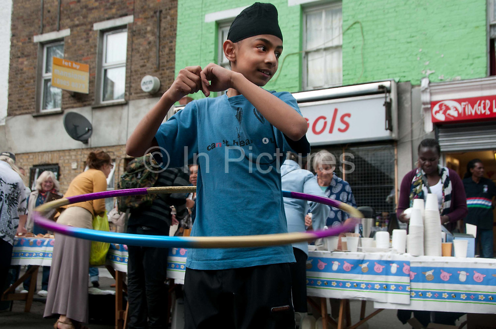 Clarence Road Hackney. Street tea party one week after the riots. Young people are given hula hoops to play with.