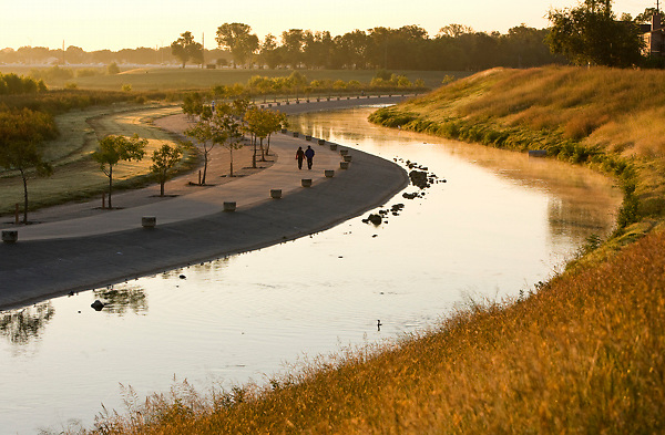 Couple walking along the bayou at sunset in Storey Park in Houston, Texas