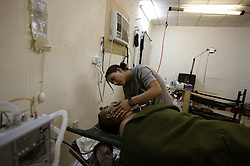 """Medical specialist Sgt. Lisa Sanchez of Company C, 407th Forward Support Battalion, 82nd Airborne Division, comforts Ed Emad Eada, Baghdad, Iraq, Aug. 10, 2003. Eada an Iraqi translator for the 82nd Airborne, recovers after surgery needed when he was shot in the arm for aiding Americans outside his home in Baghdad. """"When you treat someone you know you try hard not to let it phase you, but afterwards it hits you,"""" said Sanchez of treating her friend Eada."""
