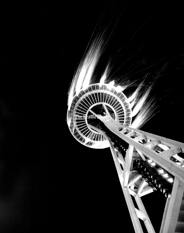 The Space Needle commemorates the 10th anniversary of the Seattle World's Fair. A brisk wind carries streams of downward-pointing white fountain fireworks. (Johnny Closs / The Seattle Times, 1972)