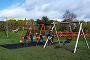 Children playing on swings in a playground outside Beaumaris Castle, on 17th of February 2020 in Beaumaris, Anglesey, Wales.