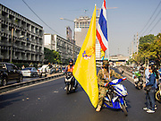 26 DECEMBER 2013 - BANGKOK, THAILAND: A protestor on a motorcycle tries to block Rama IX Road near the Thai Japan Stadium. Thousands of anti-government protestors flooded into the area around the Thai Japan Stadium to try to prevent the drawing of ballot list numbers by the Election Commission, which determines the order in which candidates appear on the ballot of the Feb. 2 election. They were unable to break into the stadium and ballot list draw went as scheduled. The protestors then started throwing rocks and small explosives at police who responded with tear gas and rubber bullets. At least 20 people were hospitalized in the melee and one policeman was reportedly shot by anti-government protestors.      PHOTO BY JACK KURTZ