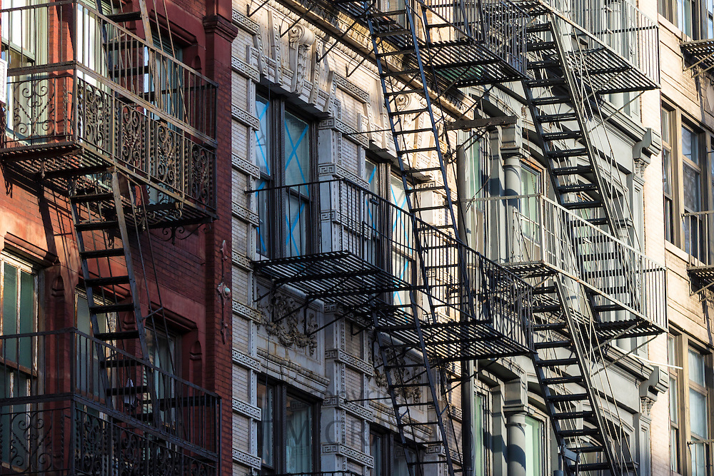 Fire Escape ladders as escape route of tenement blocks of city apartments in Soho in New York, USA