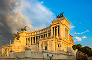 """The Altare della Patria, also known as the Monumento Nazionale a Vittorio Emanuele II (""""National Monument to Victor Emmanuel II"""") or Il Vittoriano, is a monument built in honor of Victor Emmanuel, the first king of a unified Italy, located in Rome, Italy. It occupies a site between the Piazza Venezia and the Capitoline Hill.<br /> <br /> The eclectic structure was designed by Giuseppe Sacconi in 1885; sculpture for it was parceled out to established sculptors all over Italy, such as Leonardo Bistolfi and Angelo Zanelli. It was inaugurated in 1911 and completed in 1925.<br /> <br /> The Vittoriano features stairways, Corinthian columns, fountains, an equestrian sculpture of Victor Emmanuel and two statues of the goddess Victoria riding on quadrigas. The structure is 135 m (443 ft) wide and 70 m (230 ft) high. If the quadrigae and winged victories are included, the height reaches 81 m (266 ft). It has a total area of 17,000 square metres.<br /> <br /> The base of the structure houses the museum of Italian Unification. In 2007, a panoramic lift was added to the structure, allowing visitors to ride up to the roof for 360-degree views of Rome."""