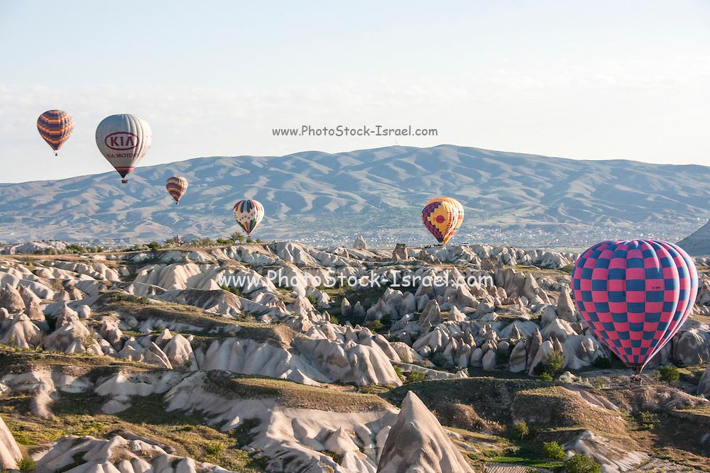 hot air balloons rise over the chimneys rock formation, Cappadocia, Turkey