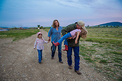 "The Nature Conservancy's Matador Ranch Operations Manager Charlie Messerly, his wife Jolynn and daughters Layla, 5, and Janae relax after a long day working with  ranching families in Eastern Montana  at the Matador ranch ""grass bank"". The ""grass bank"" is an innovative way to leverage conservation gains, in which ranchers can graze their cattle at discounted rates on Conservancy land in exchange for improving conservation practices on their own ""home"" ranches. In 2002, the <br /> Conservancy began leasing parts of the ranch to neighboring ranchers who were suffering from  severe drought, offering the Matador's grass to neighboring ranches in exchange for their  participation in conservation efforts. The grassbank has helped keep ranchers from plowing up native grassland to farm it; helped remove obstacles to pronghorn antelope migration; improved habitat for the Greater Sage-Grouse and reduced the risk of Sage-Grouse colliding with fences; preserved prairie dog towns and prevented the spread of noxious weeds. (Photo By Ami Vitale)"