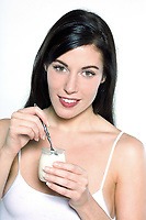 one beautiful young caucasian woman eating yogurt on isolated background eating yogourt