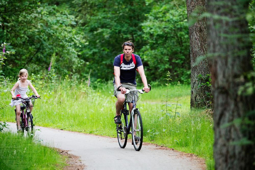 In de bossen bij Soest rijdt een man met zijn dochter op de fiets.<br /> <br /> In the woods near Soest a man is cycling with his daughter.