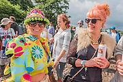 A woman wears a unique psycedelic coat with teddy bears as shoulder pads - The 2016 Glastonbury Festival, Worthy Farm, Glastonbury.