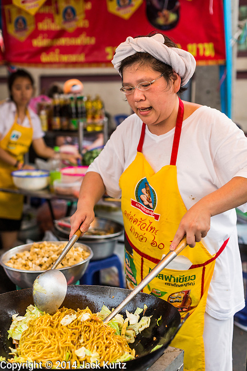 24 SEPTEMBER 2014 - BANGKOK, THAILAND: A woman stir fries vegetarian noodles during the Vegetarian Festival in Bangkok. The Vegetarian Festival is celebrated throughout Thailand. It is the Thai version of the The Nine Emperor Gods Festival, a nine-day Taoist celebration beginning on the eve of 9th lunar month of the Chinese calendar. During a period of nine days, those who are participating in the festival dress all in white and abstain from eating meat, poultry, seafood, and dairy products. Vendors and proprietors of restaurants indicate that vegetarian food is for sale by putting a yellow flag out with Thai characters for meatless written on it in red.    PHOTO BY JACK KURTZ