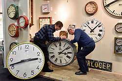 © Licensed to London News Pictures. 03/10/2017. London, UK. Gallery owners from Clockprops.com prepare to hang an antique clocks at the Decorative Antiques & Textiles Fair taking place at Evolution in Battersea Park which runs 3-8 October 2017 and features more than 160 exhibitors.  Photo credit : Stephen Chung/LNP