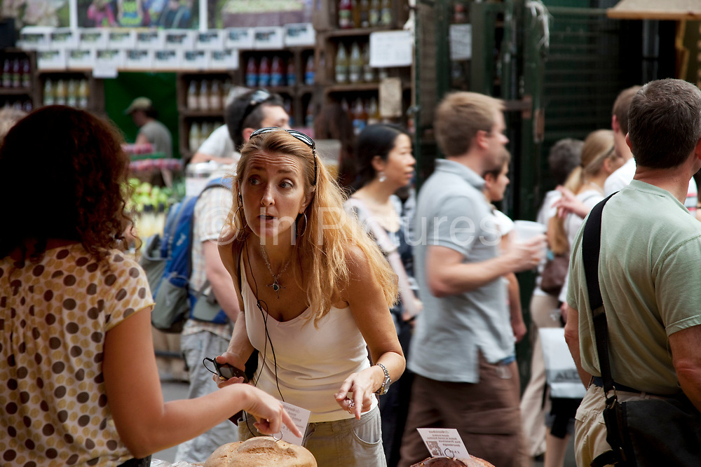 Woman speaks to a bakery stall holder. Borough Market is a thriving Farmers market near London Bridge. Saturday is the busiest day.
