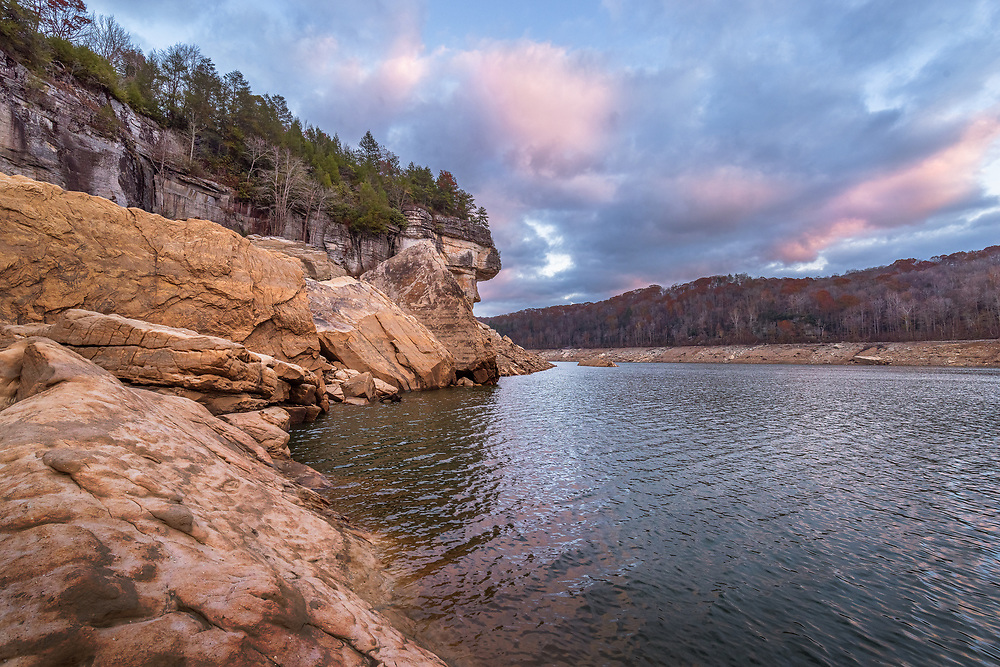 The low waters of Summersville Lake of West Virginia, drained to winter pool, reveal the mammoth sandstone rock formations rising from the edges of the great lake on a late autumn evening.