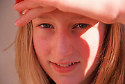 A793KC Young girl shielding the sun from her face with her hand and looking directly at the camera