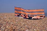 AJDNDB Elderly couple sunbathing by windbreak Shingle Street Suffolk England