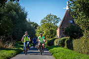 A group of male and female cyclists tour around Staplehurst, Kent, England, UK on electric bikes.  They pass a traditional Oast house, famous across the county of Kent and Surrey.