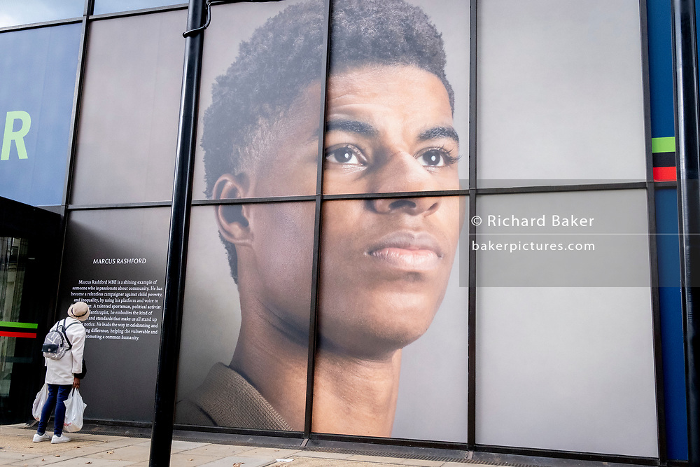 A woman of colour reads a caption beneath the large billboard, a portrait of English football player, Marcus Rashford, outsidee the Strand branch of Coutts Bank, on 14th October, 2021, in Westminster, London, England. Marcus Rashford has recently been awarded an honourary degree by The University of Manchester in recognition of his political campaigning on behalf of the underprivilged (in particular, of school meals) and his philanthropy. He currently plays for Manchester United and is in the English national team. He has also been the victim of online racial abuse.