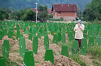 A Bosnian woman looks for the names of loved ones that have been reburied in the Potocari Memorial Center, outside of Srebrenica, Bosnia. Those buried in Potocari were victims of the Srebrenica massacre and were originally buried in mass graves.